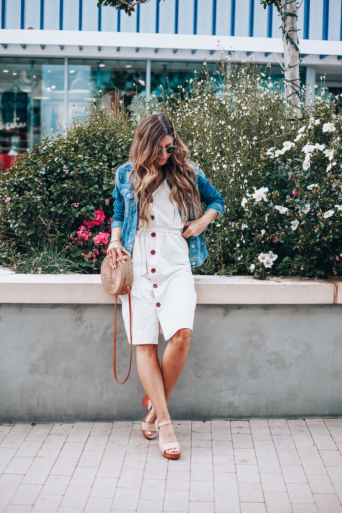 denim jacket on top of white dress worn by woman with long wavy hair cotton summer dresses beige sandals bag sunglasses