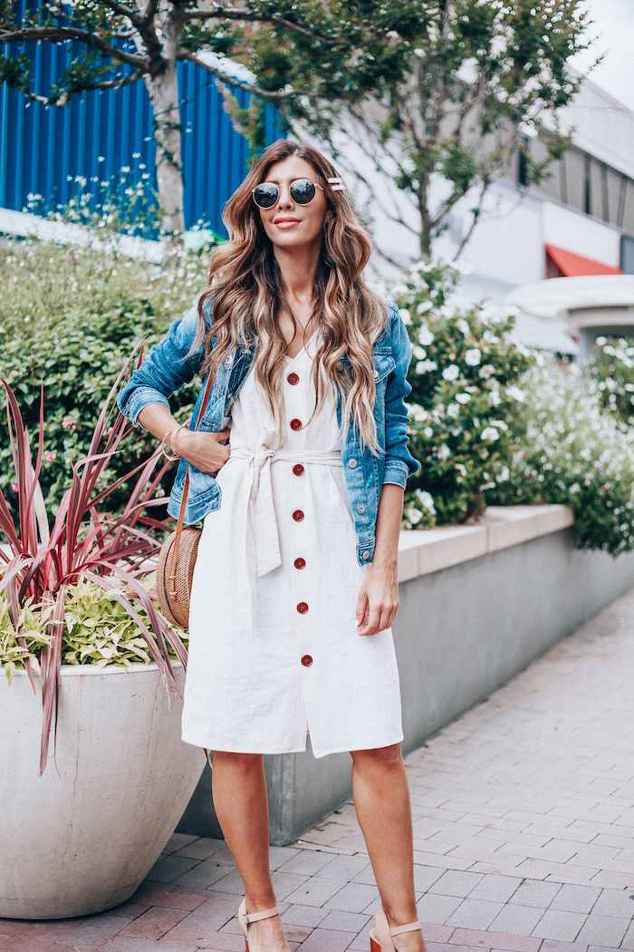 denim jacket on top of white dress worn by woman with long wavy hair cotton summer dresses beige sandals bag