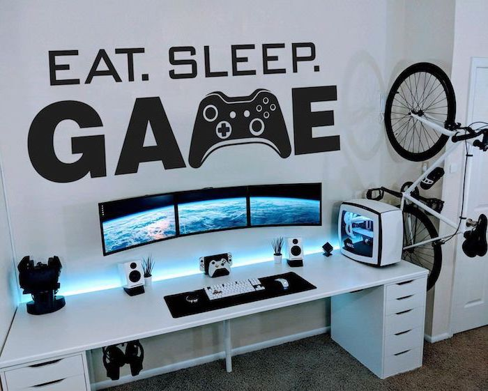 eat sleep game sticker on white wall white wooden desk teen boy room ideas gaming setup with three monitors bike on the side