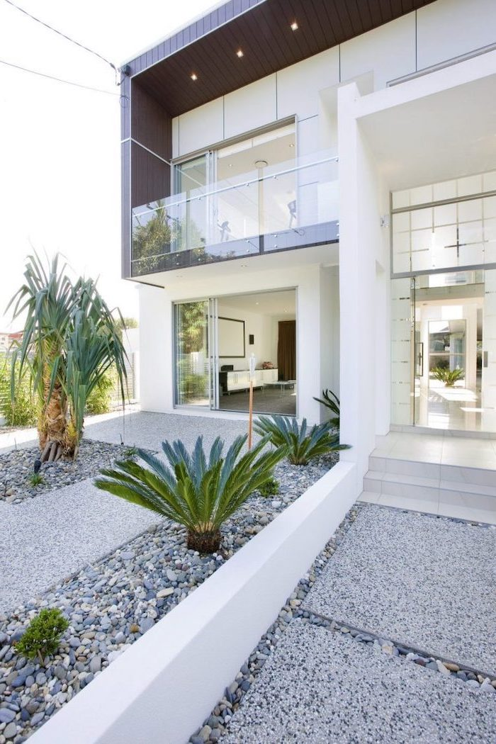 facade of two storey house front yard landscaping ideas tiled gravel pathway leading to the front door palm trees planted in the gravel