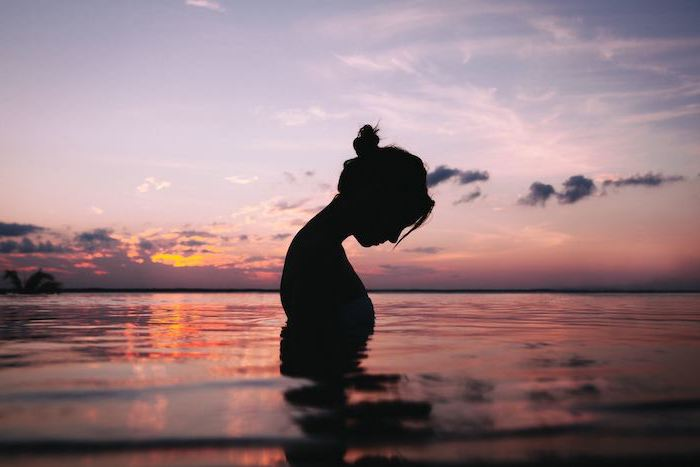 female silhouette at sunset cute aesthetic wallpapers woman standing in the water with hair in a bun