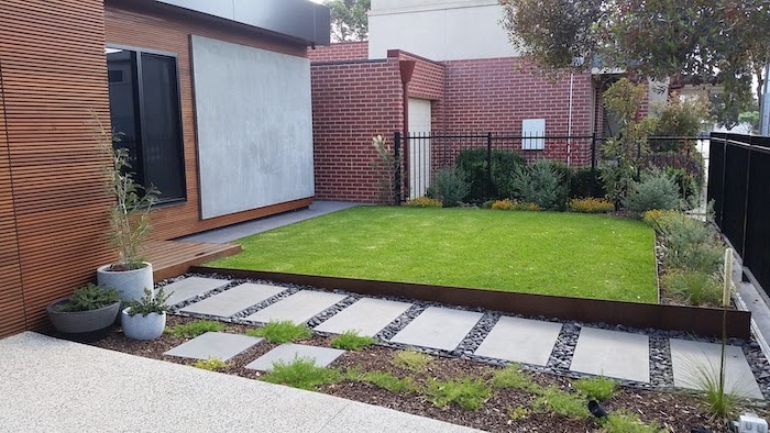 front of house landscaping pathway between gate and front door tiles in gravel with bushes and grass around