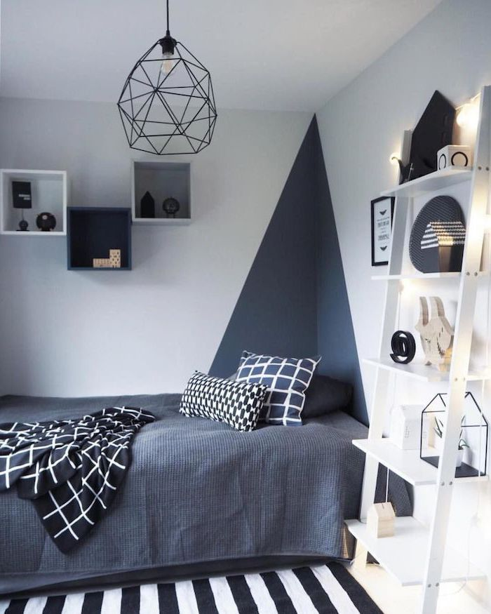 geometric wall design bookshelves on the walls boys room colors dark grey bed sheets white wooden bookcase next to the bed