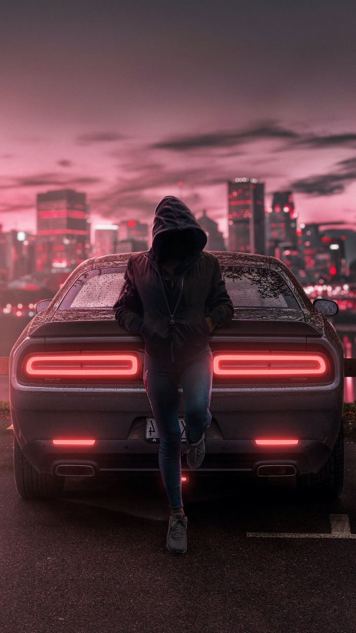 girl wearing jeans and black hoodie leaning on dodge challenger wallpapers for guys city skyline in the background
