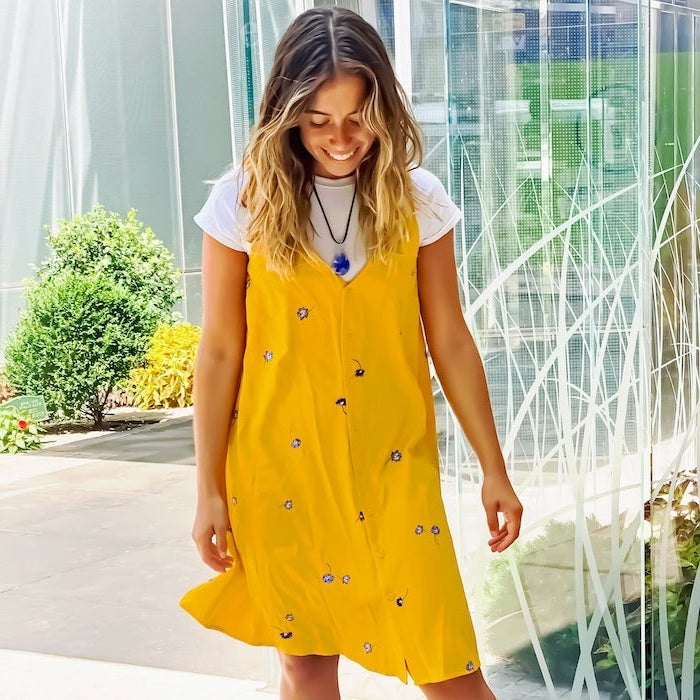 girl with balayage hair wearing white t shirt under yellow dress with blue flowers womens casual summer dresses standing on sidewalk