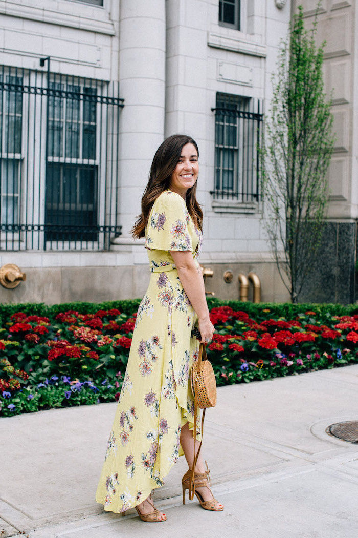 girl with dark brown hair wearing long yellow dress with purple flowers summer wedding guest dresses brown sandals and bag