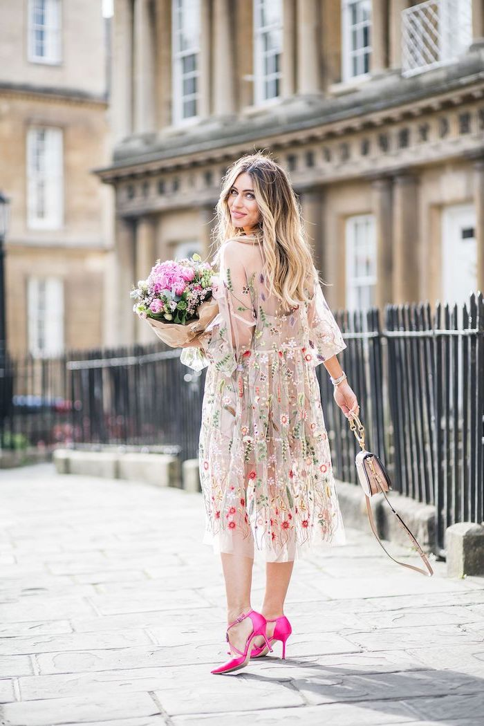 girl with long wavy balayage hair beach wedding guest dresses wearing nude tulle dress with flowers pink shoes holding a bouquet of flowers