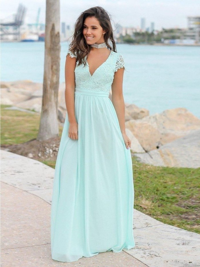 girl with medium length brown wavy hair wearing long blue dress with lace top wedding guest outfits standing on a pier