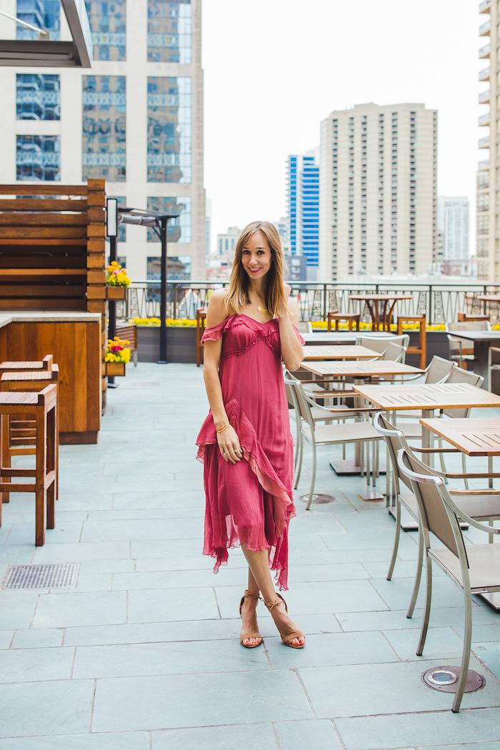 girl with medium length dark blonde hair summer wedding guest dresses wearing dark pink midi dress standing on balcony