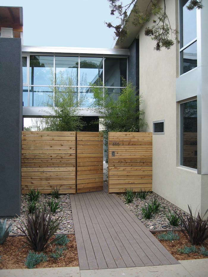 gravel on both sides of wooden pathway simple landscaping ideas leading to wooden gate with bushes planted on both sides