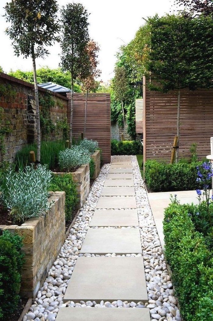 gravel pathway with white tiles small front yard ideas surrounded by flower beds and bushes and trees