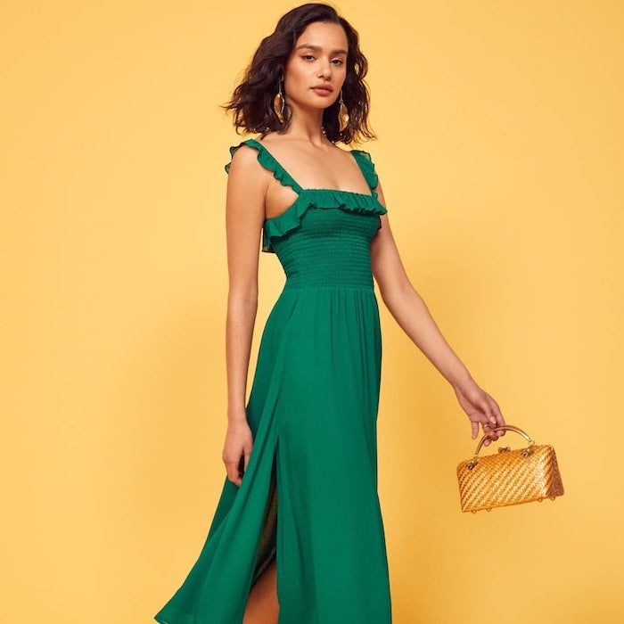 green dress worn by woman with shoulder length wavy brown hair elegant dresses for wedding guests small gold bag
