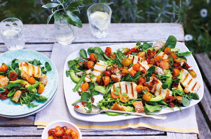 grilled halloumi cheese with spinach halved cherry tomatoes cucumbers easy salad recipes white plate on wooden table