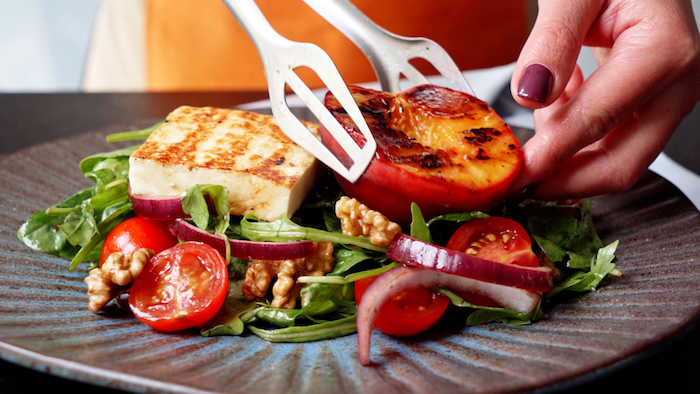 grilled peach and halloumi being placed on top of arugula summer salad recipe with onion cherry tomatoes walnuts