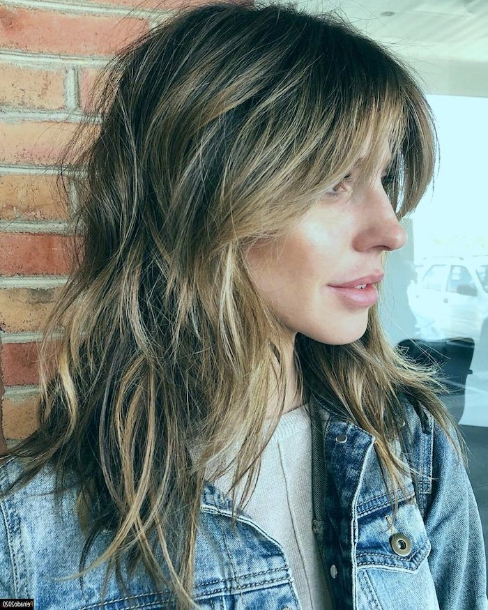 haircuts for thin hair woman with brunette hair with blonde highlights with bangs wearing denim jacket