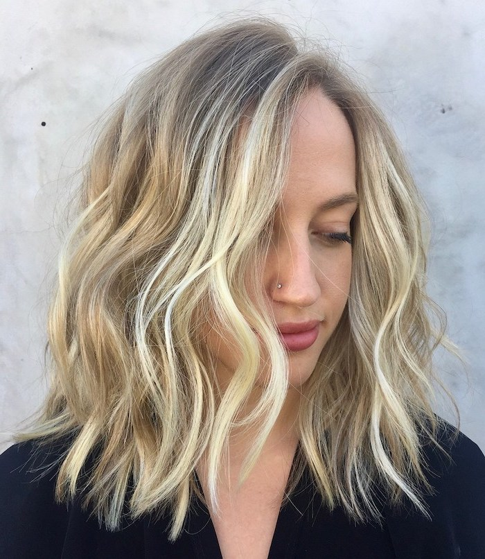 hairstyles for medium hair woman with blonde wavy hair with blonde highlights wearing black blazer with nose piercing
