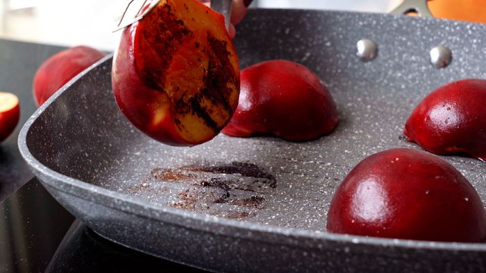 halved peaches being grilled onto a gray grill pan summer salad recipe held with tongs