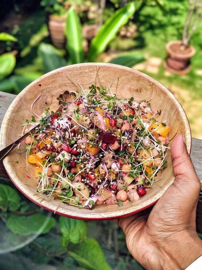 healthy salad recipes sprouts chickpeas sesame seeds mango pomegranate seeds inside wooden bowl