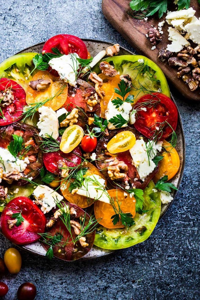 heirloom tomatoes with dill walnuts feta cheese summer salads placed on dark surface
