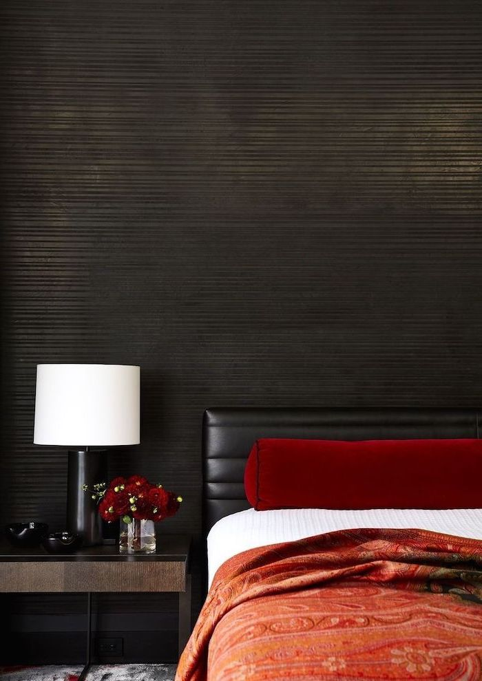 how to decorate a bedroom black wall black leather bed frame red blanket red velvet throw pillows dark wooden night stand