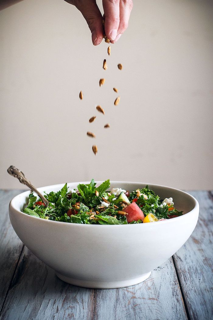 kale salad with watermelon halved cherry tomatoes seeds different types of salads inside white bowl on wooden table