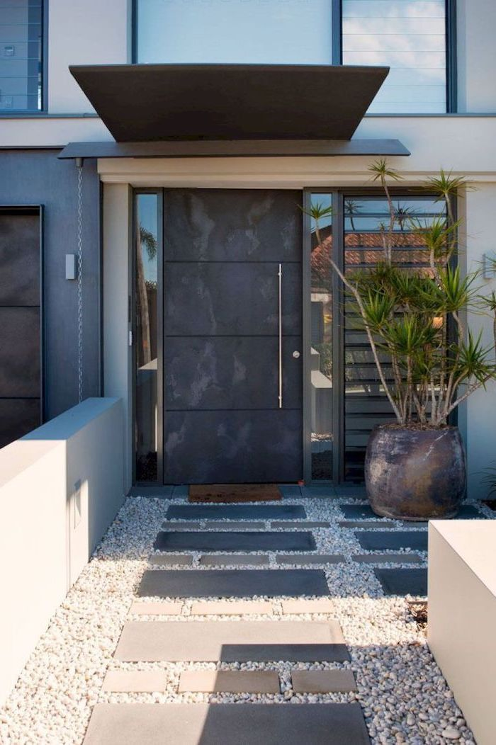 large black door front of house landscaping pot with palm tree next to it tiled gravel pathway