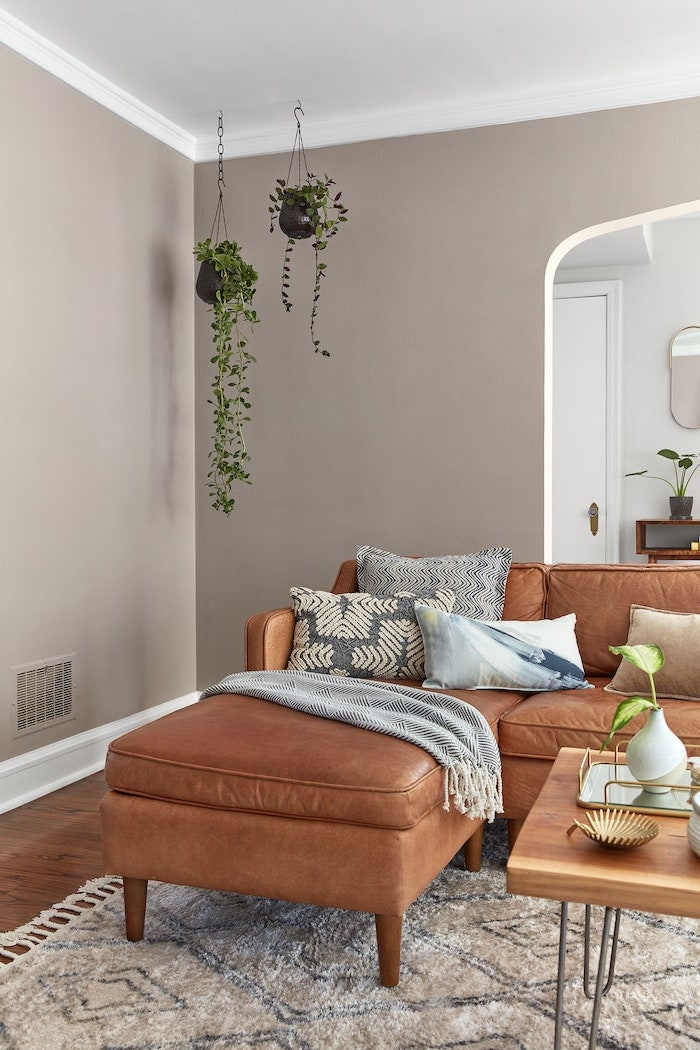 living room paint color ideas brown leather corner sofa with blue white and black throw pillows light gray walls wooden floor