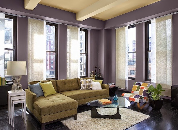 living room paint colors purple walls with tall windows green corner sofa colorful armchair black wooden floor white carpet