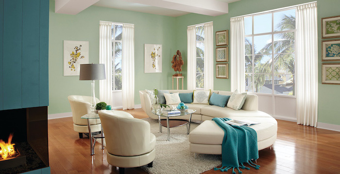 living room wall colors light mint green walls with tall windows white sofa with turquoise white throw pillows white armchairs wooden floor