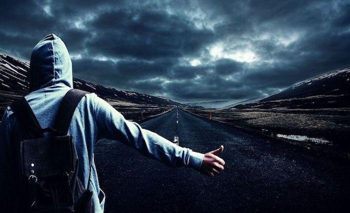 man hitchhiking on empty road wearing grey hoodie black backpack cool phone wallpapers dark sky