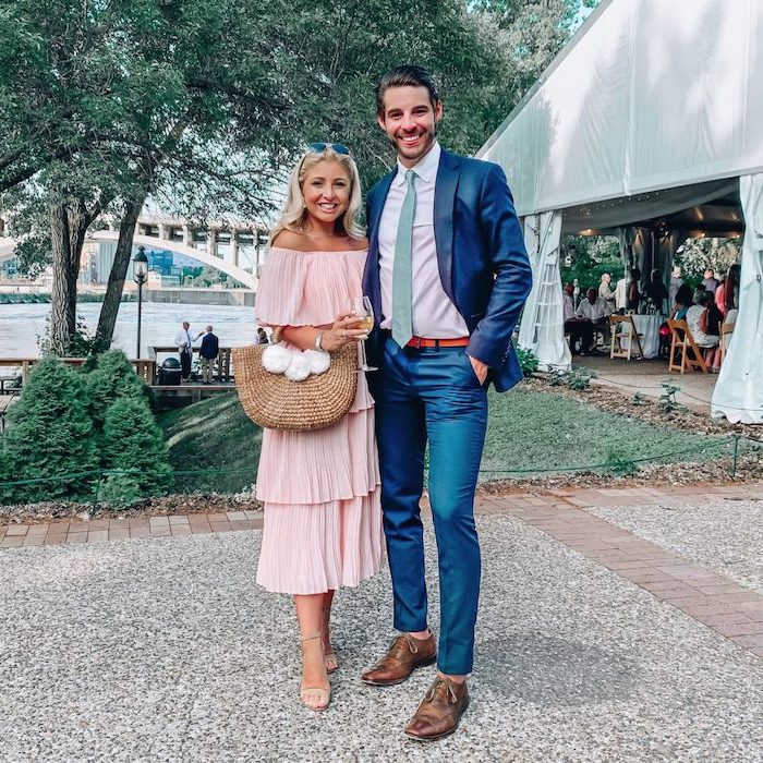man wearing suit woman wearing pleated strapless pink midi dress elegant dresses for wedding guests standing next to large tent