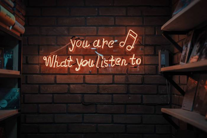 neon sign on brick wall next to wooden bookshelves cute wallpapers for girls you are what you listen to