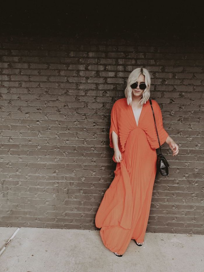 orange long pleated dress worn by woman with short wavy blonde hair long sleeve wedding guest dresses black sandals and leather crossbody bag