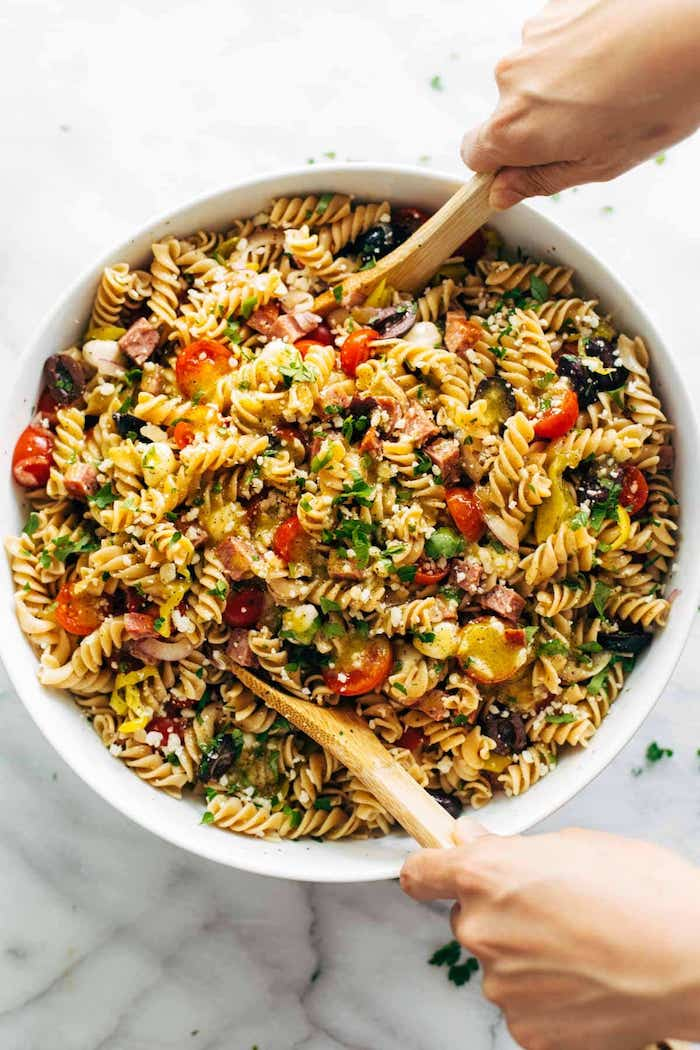 pasta salad with halved cherry tomatoes bacon olives how to make salad italian pasta salad in white bowl two wooden spoons