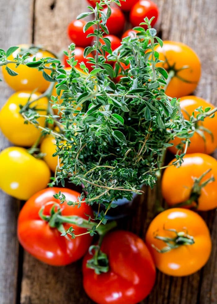 red and yellow cherry tomatoes with branches different types of salads placed on wooden table