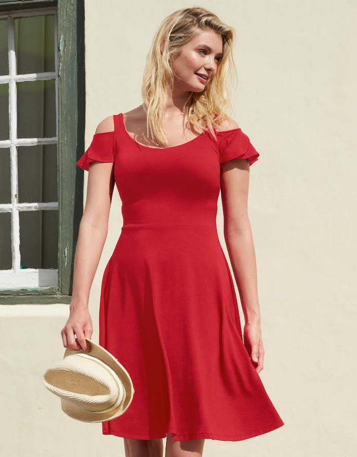 red dress worn by woman with short wavy blonde hair summer beach dresses carrying a hat
