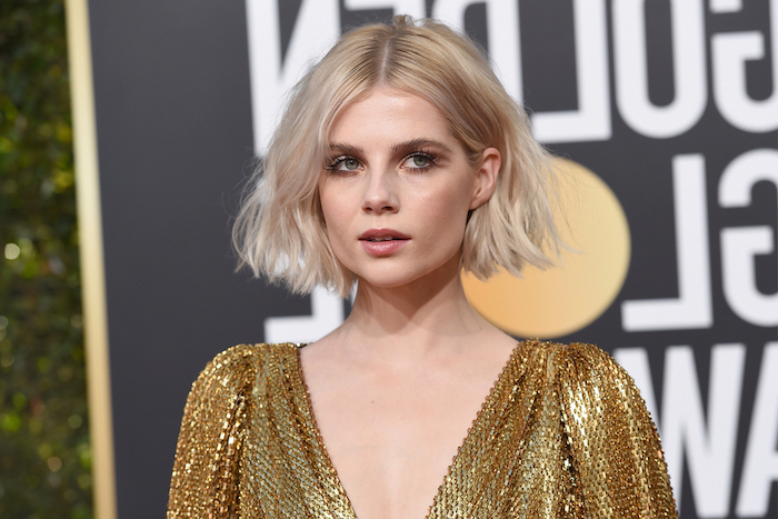 short hairstyles for thin hair lucy boynton on the red carpet wearing golden dress with short blonde hair with slight curls