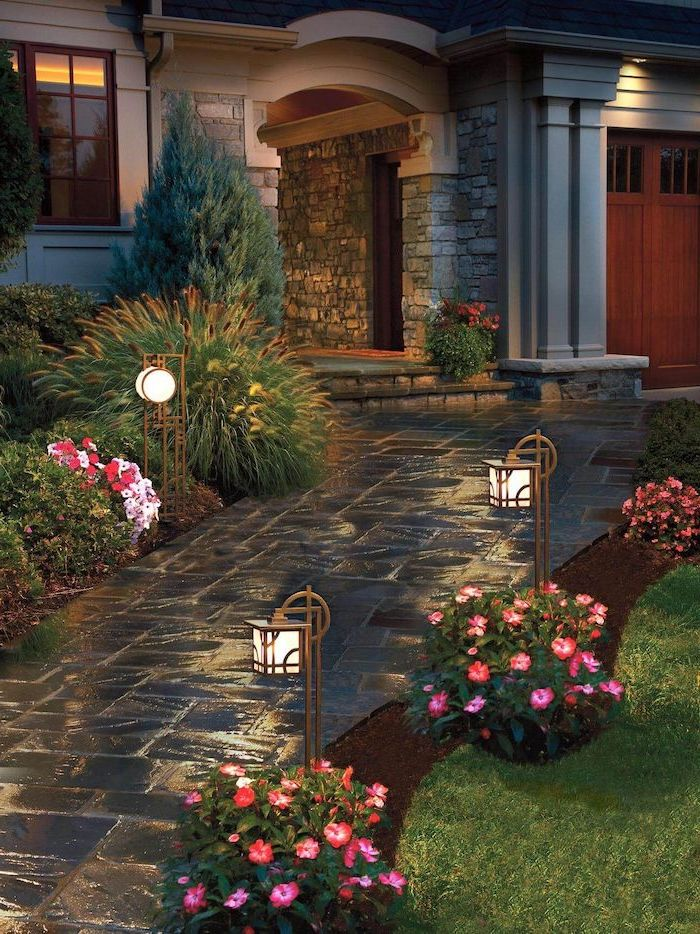 simple landscaping ideas stone tiled pathway leading to the front door flower beds bushes and garden lamps on both sides