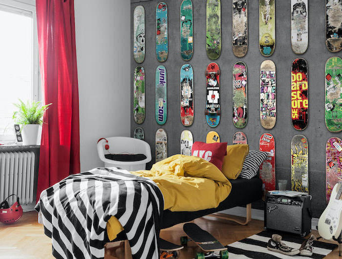 skateboard shaped metal plaques arranged hanging on grey wall behind the bed boys bedroom furniture wooden floor with guitar stand and two skateboards