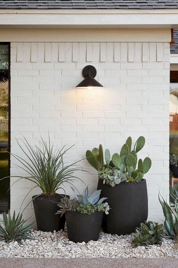 small front yard ideas three black ceramic pots with different succulents inside arranged in front of white brick wall on rocks