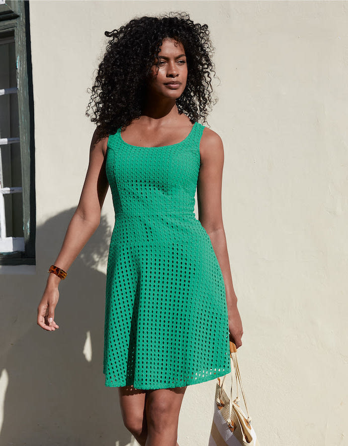 summer beach dresses woman with curly black hair wearing green dress standing on the sidewalk