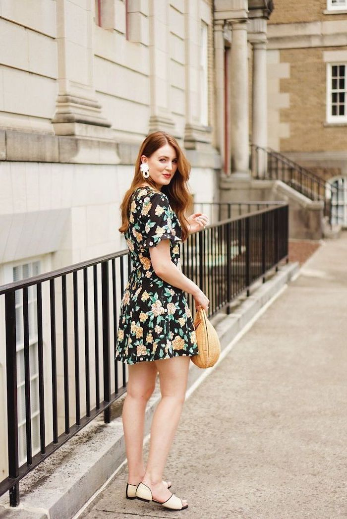 summer maxi dresses woman with ginger hair wearing black dress with yellow orange flowers standing on the sidewalk