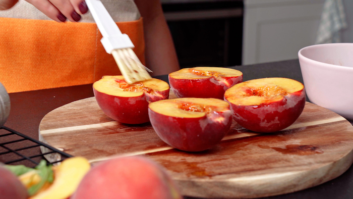 summer salad recipe halved peaches being covered with dressing arranged on wooden cutting board
