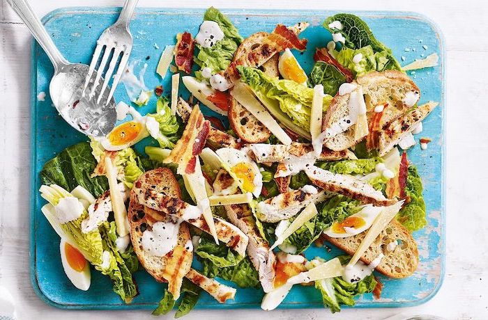 summer salad recipes ceasers salad with chicken strips bacon boiled eggs placed on blue wooden board