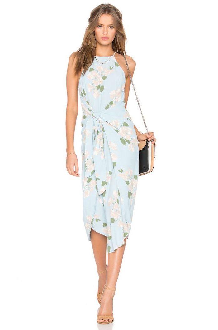 summer wedding guest dresses woman with medium length dark blonde wavy hair wearing blue dress with white flowers
