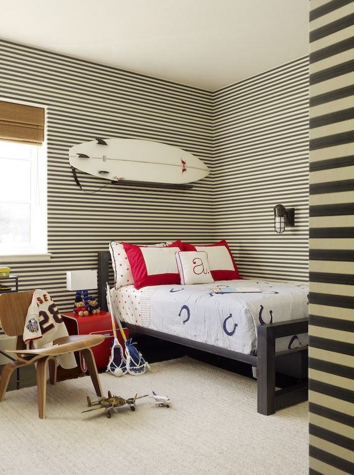 teen boy bedroom furniture surf hanging on the wall above the bed walls in black and white stripes lacrosse gear on wooden chair
