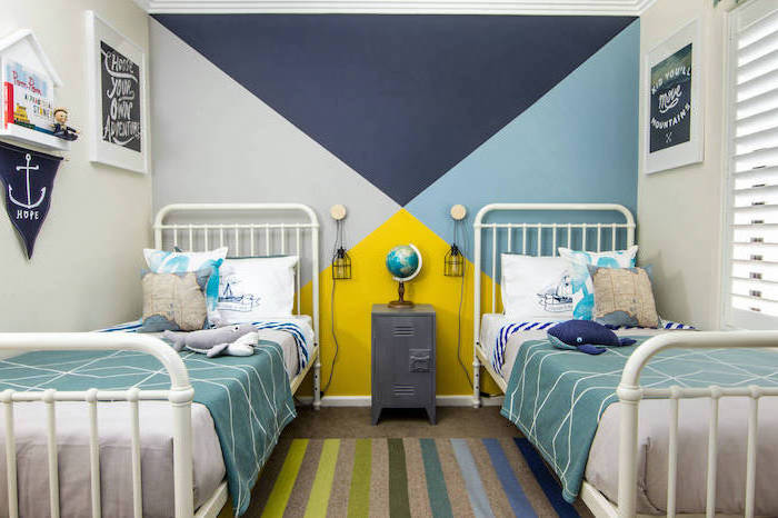 two beds with white metal frames boys bedroom decor geometric accent wall behind them in shades of blue and yellow colorful carpet