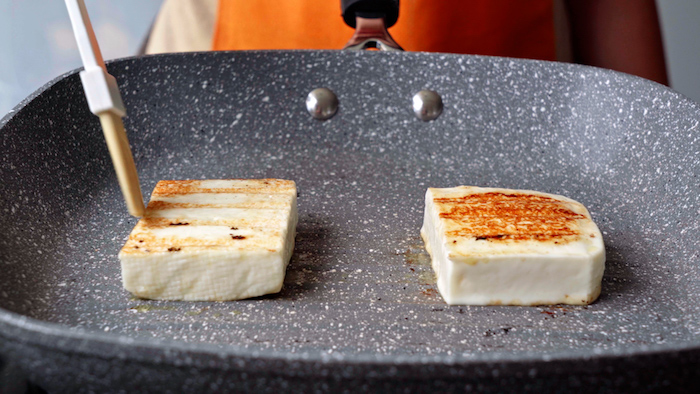 two slices of halloumi cheese being grilled onto a gray grill pan summer salad recipe