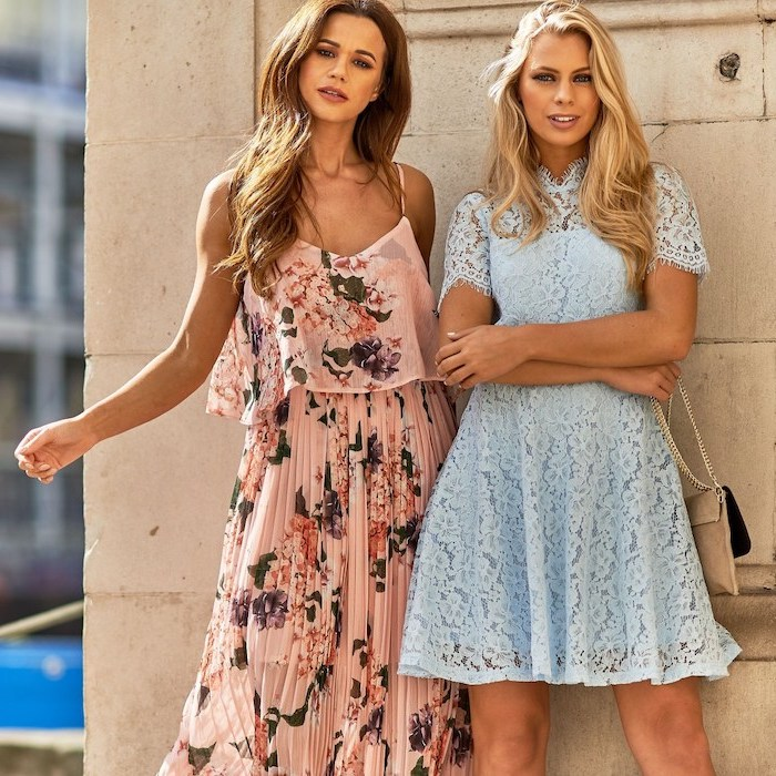 two women with blonde wavy hair beach wedding guest dresses one wearing pink pleated dress with flowers other wearing blue lace dress