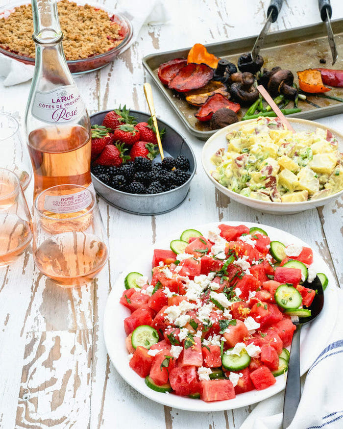 watermelon cucumber feta cheese salad in white plate healthy salad recipes rose bottle on white wooden table